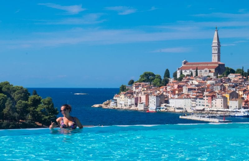 Kate sits in a sky-blue infinity pool, reading her Kindle, the skyline of Rovinj in the background, complete with its church steeple sticking above everything else, under a bright blue sky.