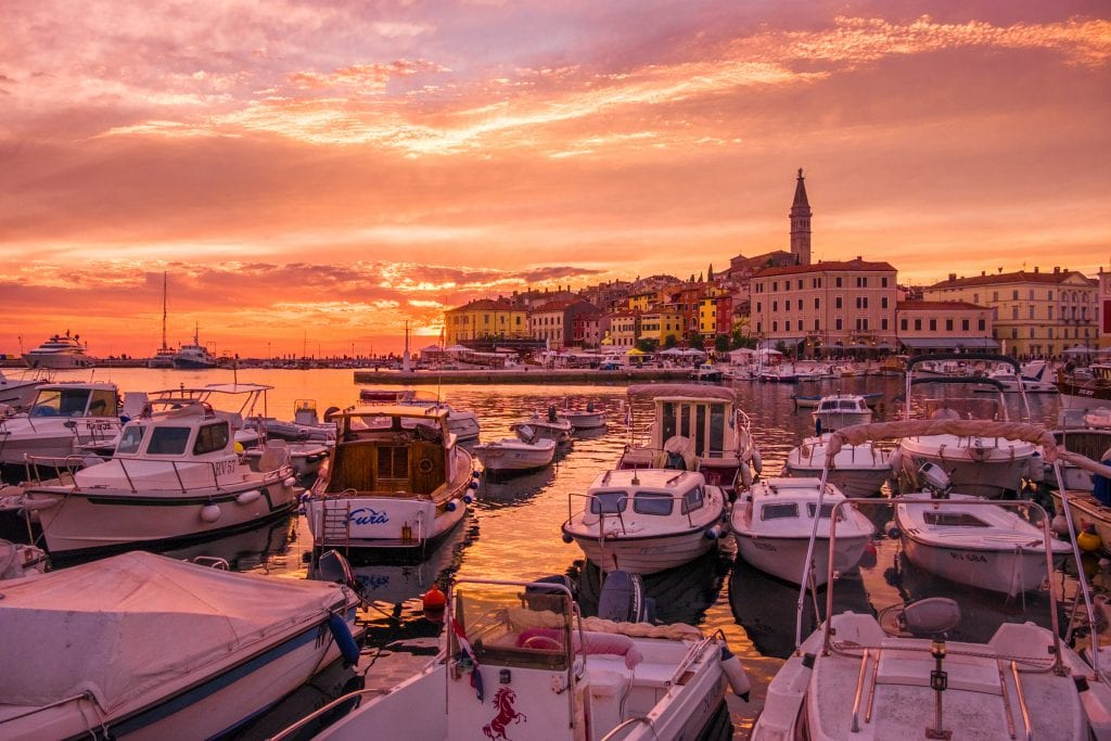 The Rovinj skyline under a bright pink and orange sunset; in the foreground are dozens of small white boats.