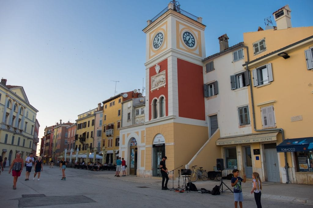 The white, red, and yellow clock tower in Rovinj, two kids talking in the foreground.