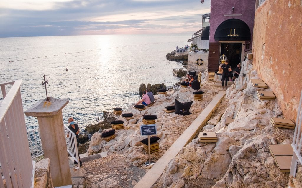 Valentino Bar: a rocky outside seating area topped with seat cushions, all on the edge of the ocean. Waiters wear face masks and serve drinks. A cloudy gray sky.