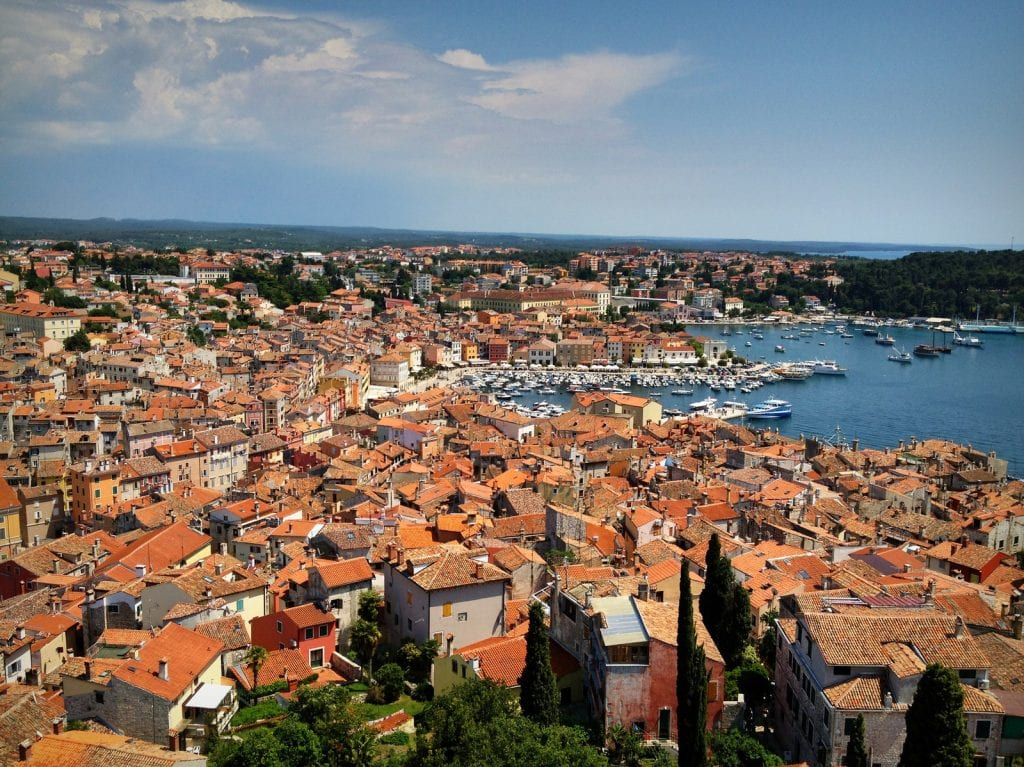 View from the top of the church in Rovinj -- layers and layers of orange terra cotta roofs, sloping down and leading to the bright blue sea.