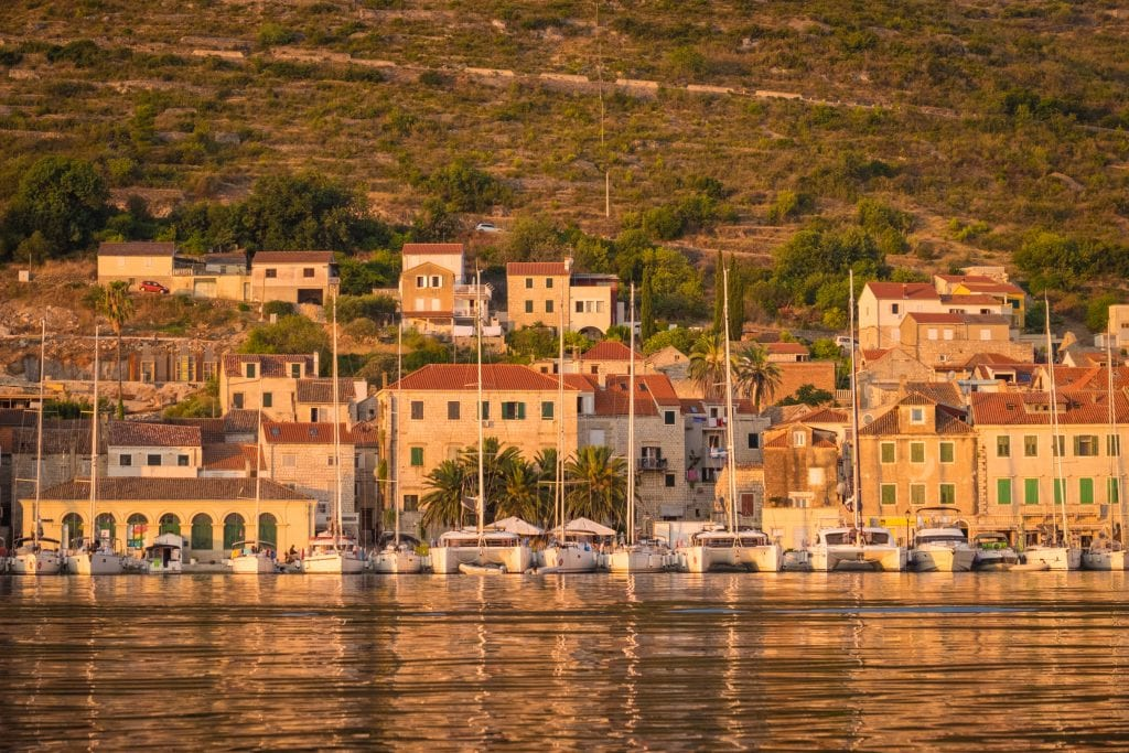 Sun-drenched stone buildings on the shore of Vis. In front of it are docked sailboats in the water.