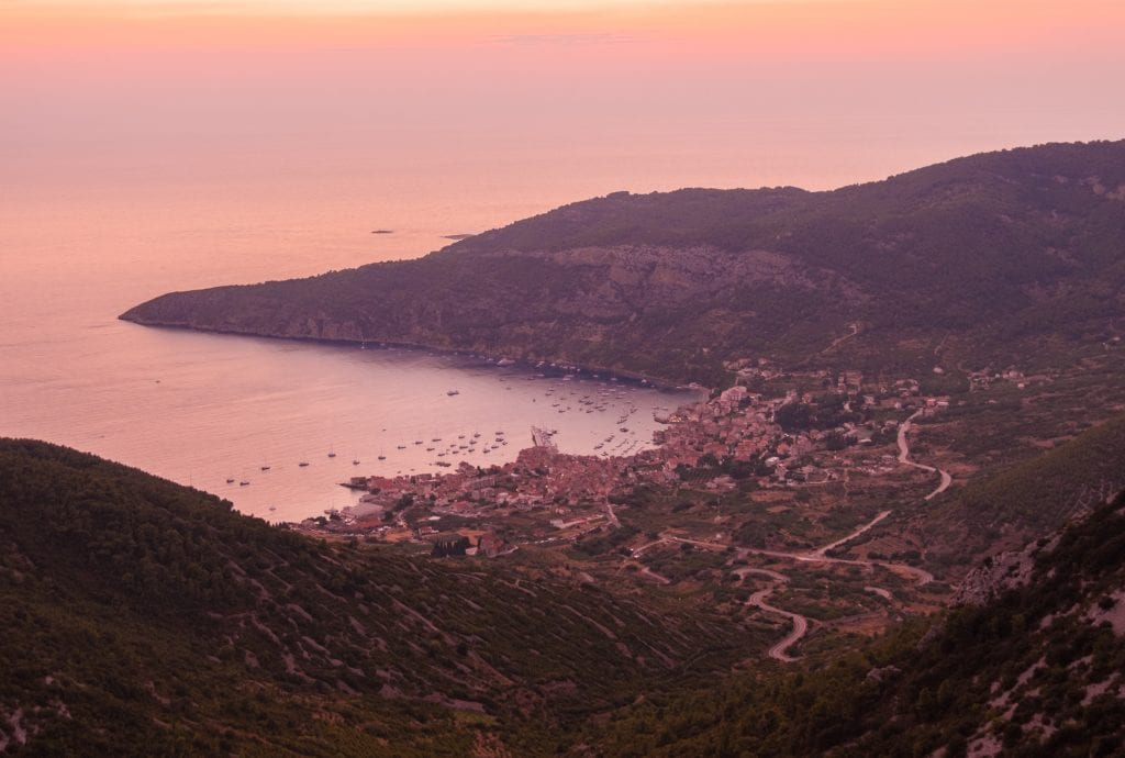 A pink sunset view of the small town of Komiža in the distance, surrounded by green hills.