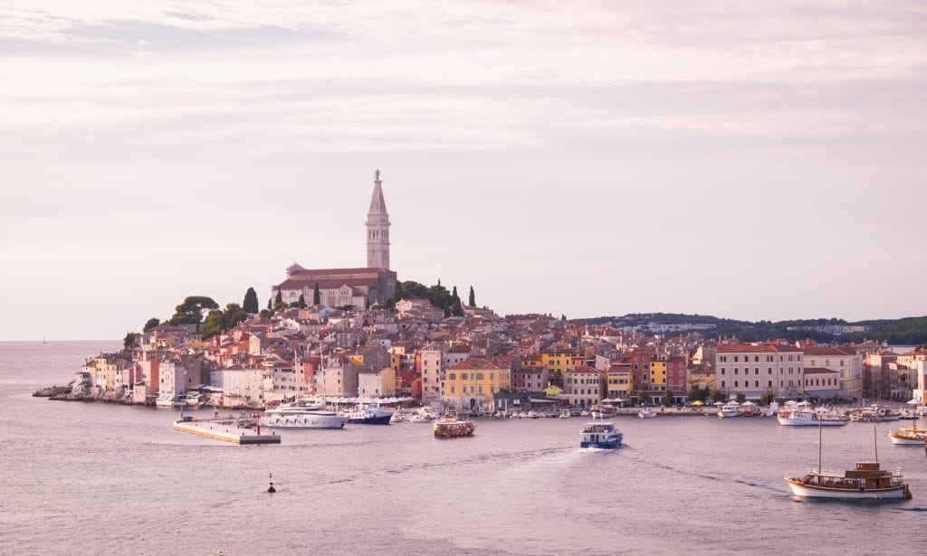 The Rovinj city skyline just before sunset: the same skyline with the warm-colored buildings along the water's edge with a church and steeple sticking straight up: the entire photo has a mild purple near-sunset tone.