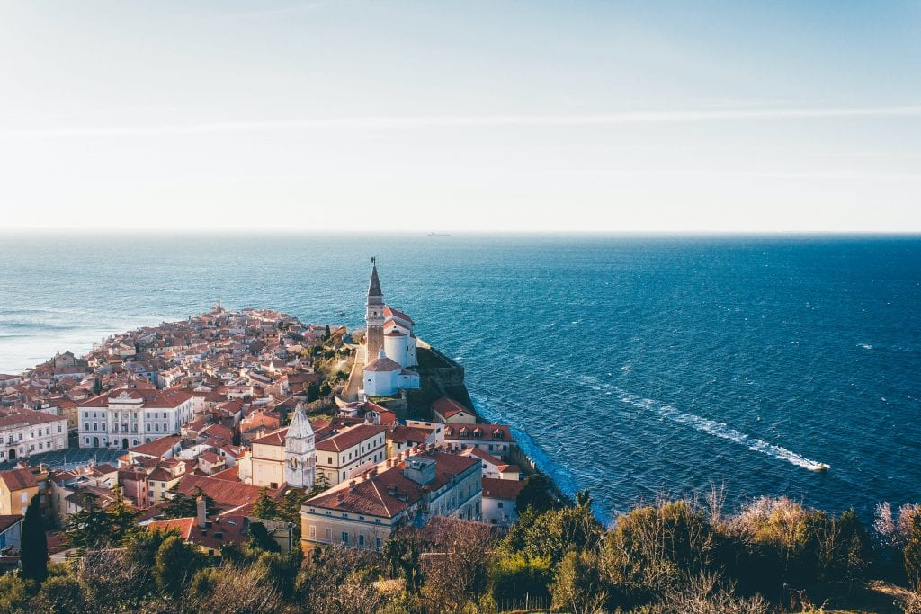 Piran, Slovenia: a town with white buildings and red roofs on the edge of the ocean.