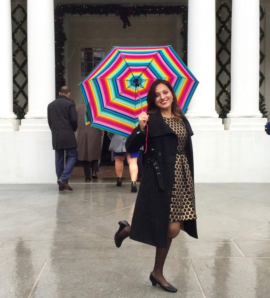 Kate wears a black and gold polka dot dress and long black peacoat, holding a rainbow striped umbrella, and smiling with one leg perched up behind her, standing in front of a White House entrance.