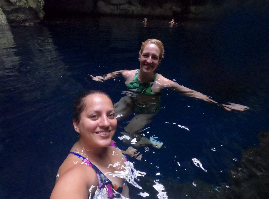Kate and Sarah float in the clear water of a cenote, surrounded by cave walls.