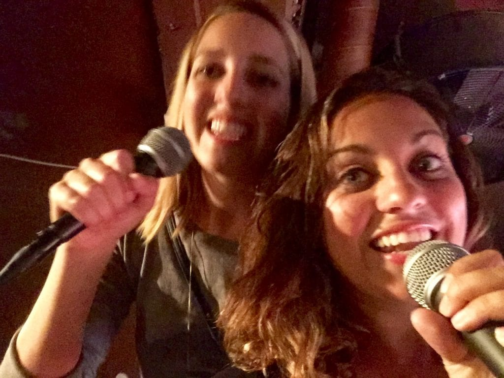 Kate and her sister Sarah singing karaoke into microphones together.