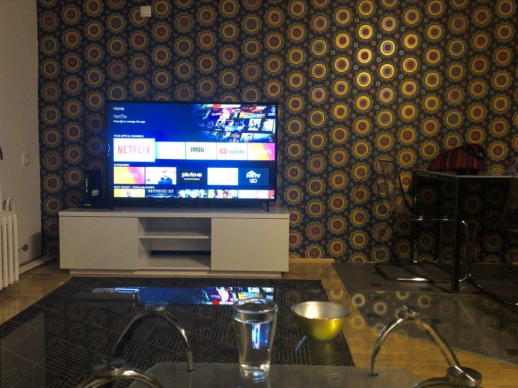 View from the couch in Novi Sad: a glass coffee table, a TV with Netflix pulled up against the wall. The wall is covered in a wild brown, gold and green 70s disco print wallpaper.