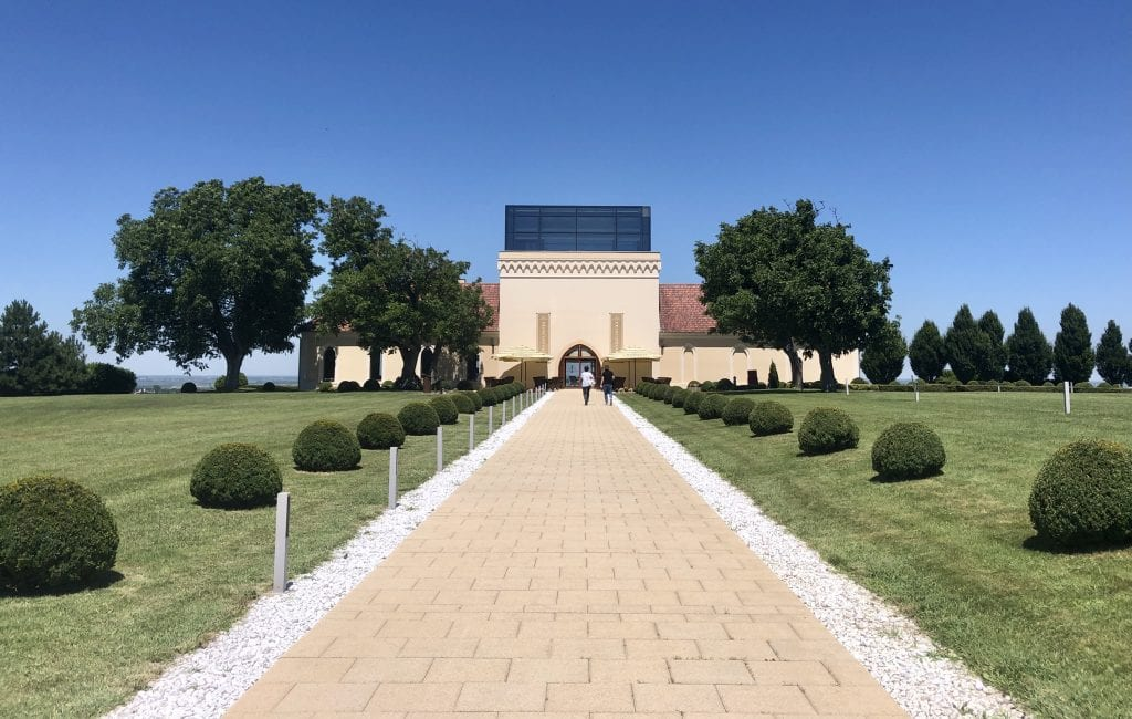 A fancy-looking winery, looking like it's almost out of California, and a stone path leading to it, surrounded by small round manicured bushes.