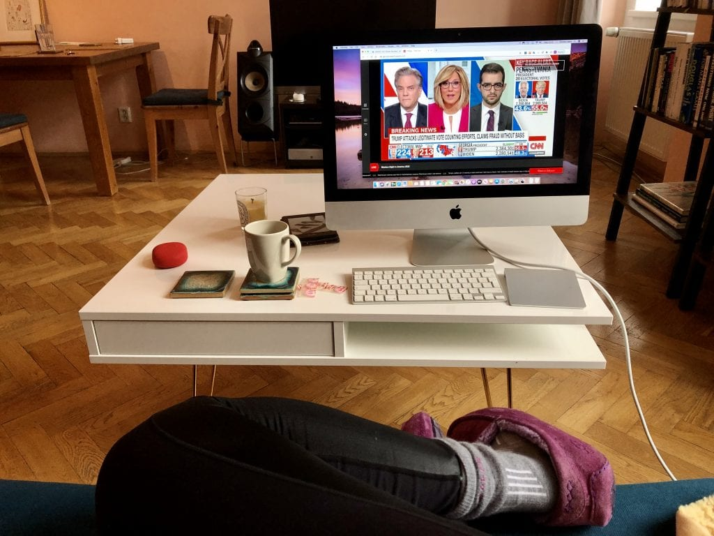 The white coffee table covered with a desktop computer and keyboard, cup of tea, kindle, candle, and packs of pepto-bismol tablets. You can see Kate's legs on the couch clad in leggings, merino wool socks, and suede slippers.