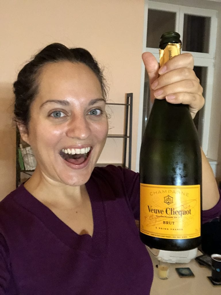 Kate holds a bottle of Veuve Clicquot champagne in her hand and has a huge smile with her mouth open.