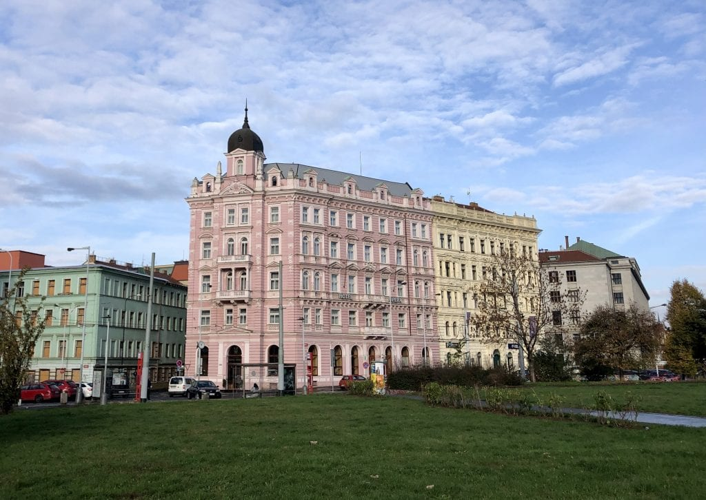 A two-tone pink crenellated building in front of a lawn in Prague, underneath a blue partly cloudy sky.