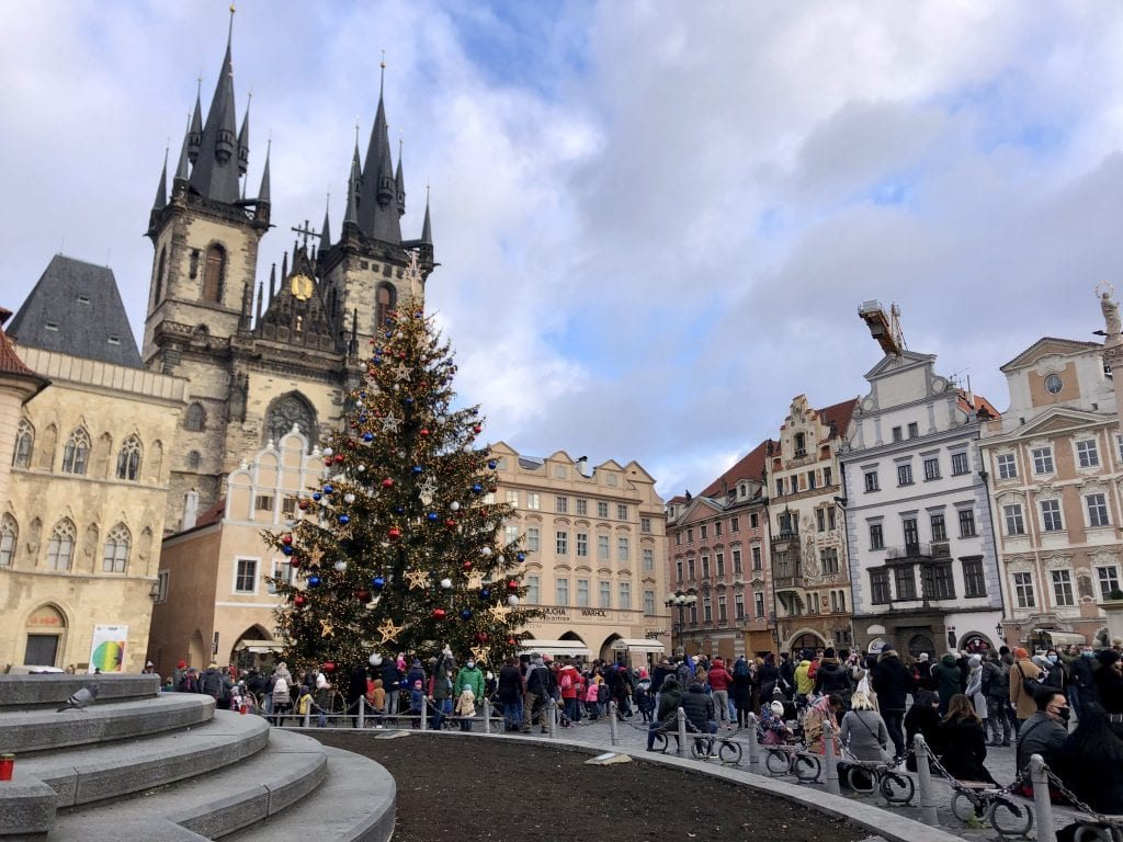 Prague's Old Town Square, with its multi-colored crenellated buildings and church steeples, and crowds around a decorated Christmas tree.