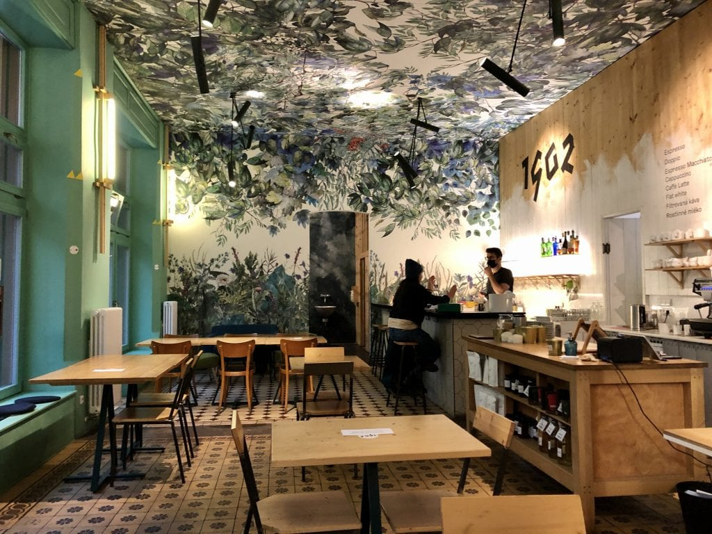 A modern cafe with wood tables and walls. On the back wall and ceiling looks like a wallpaper mural of wild overgrown green plants against a white background. A man in a black face mask serves a customer in a hoodie.