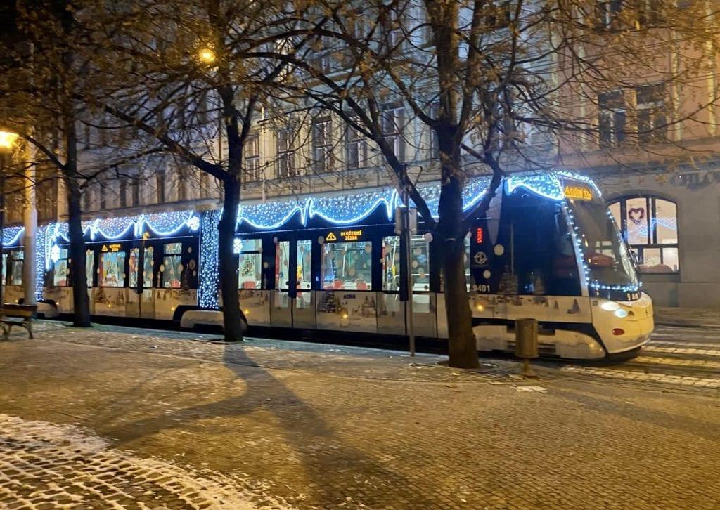 A tram on a snowy cobblestone stream in Prague. It's decorated with Christmas lights and images of Christmas trees and snowflakes painted on the side of it.