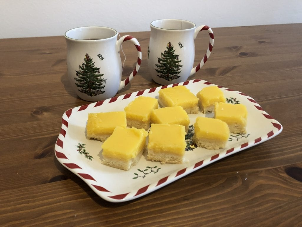 A Christmas-themed white platter with red and white striped edging topped with lemon squares, shortbread on the bottom and bright yellow curd on top. Behind the platter are two matching mugs with Christmas trees on them and red and white striped handles.