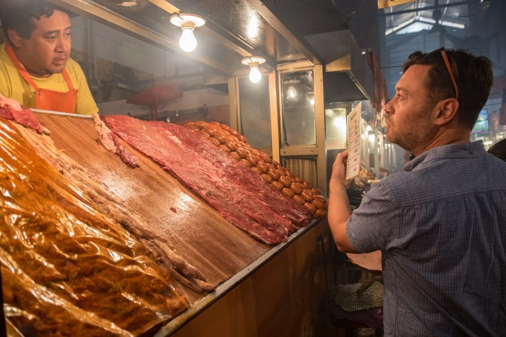 Charlie holds up a menu and talks to a butcher behind a wooden counter topped with lots of raw meat at Mercado 20 Noviembre.