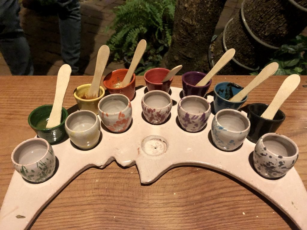 A white crescent moon-shaped plate topped with a row of seven white shot glass-sized glasses filled with mezcal, and a row of seven shot glasses painted the same colors as their moles within with wooden tasters sticking out.