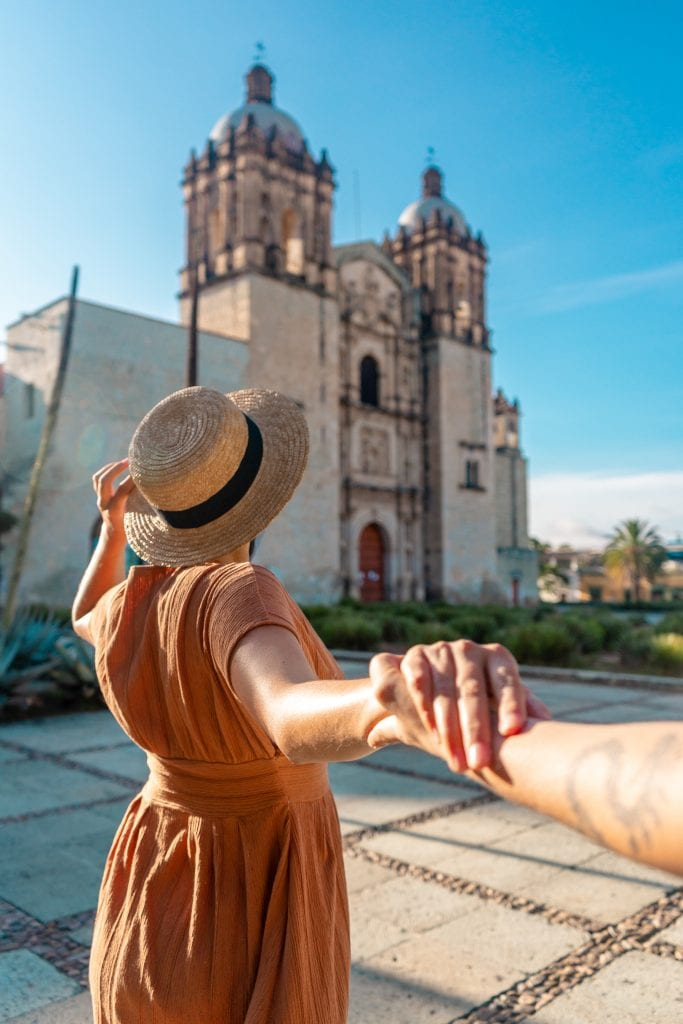 A woman posing for Instagram in front of Templo Santo Domingo in a wide-brimmed hat, holding the hand of the photographer behind her.