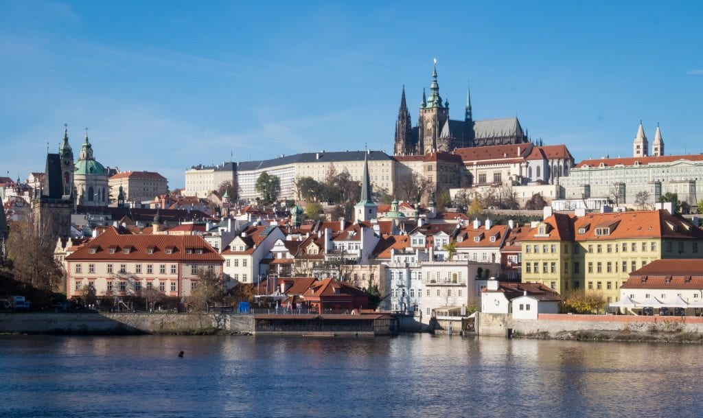 A view of Prague castle on the hill with the steeples of St. Vitus's Cathedral poking through, underneath a bright blue sky. There are lots of other colorful buildings with orange roofs, and in the foreground, the blue Vltava river.