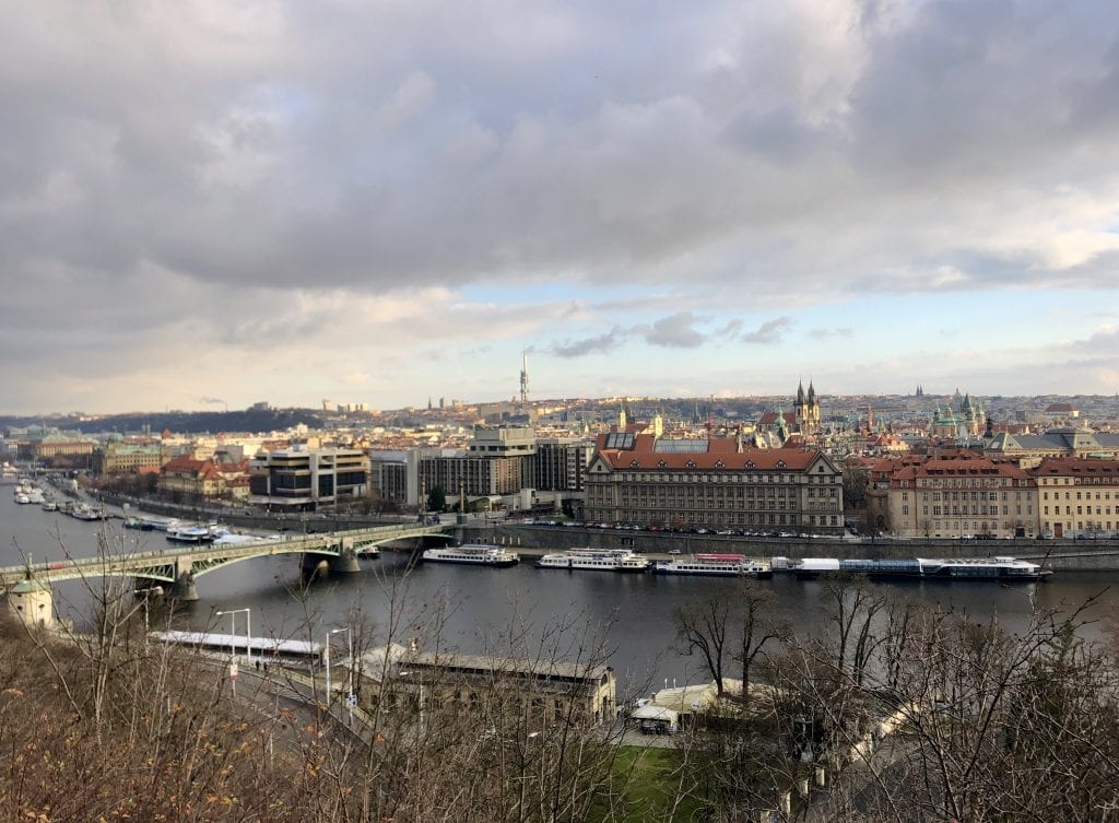 A view of Prague from a high hill in the Letna neighborhood. You see the dark gray Vltava River edged with white boats and bisected by a green bridge. Also in the background are buildings with church steeples peeking through the skyline, and the gray tube-shaped TV Tower far in the background.