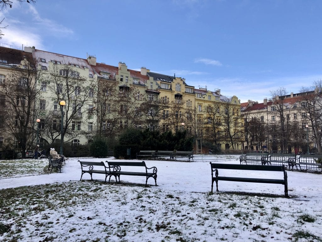A park in Prague with light snowfall on the ground, grass peeking through, wooden benches (one with a woman sitting on it in a tan winter coat), and in the background, beige, taupe, and yellow buildings underneath a bright blue sky.